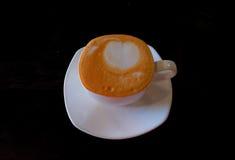 Copo de café com arte do latte no fundo preto Foto de Stock Royalty Free