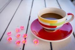 Copo de café com as flores pequenas na tabela de madeira fotografia de stock