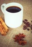 Copo de café com canela, anis e feijões imagens de stock royalty free