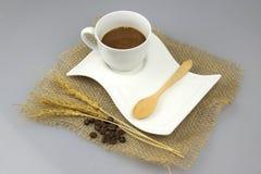 Copo de café com a colher de chá no fundo do isolado de matéria têxtil do gunny Foto de Stock