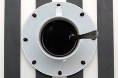 Copo de café com a colher em feijões dos pires e de café contra o fundo branco que forma o seletor de pulso de disparo Vista de a Fotos de Stock