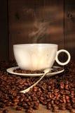 Copo de café com a colher em feijões roasted Foto de Stock Royalty Free
