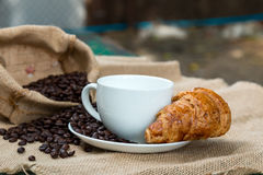 Copo de café com croissant e feijão na tabela Imagens de Stock
