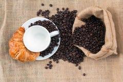 Copo de café com croissant e feijão na tabela olhando de fotografia de stock royalty free