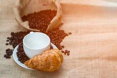 Copo de café com croissant e feijão que estão prontos para o si do café Fotografia de Stock Royalty Free