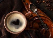 Copo de café com a forma do coração feita da espuma na tabela de madeira colonial velha, vista superior Fotografia de Stock