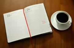 Copo de café com livro de nota Imagem de Stock Royalty Free