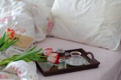Copo de café com livro e tulipas das cores na cama foto de stock royalty free
