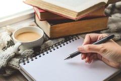 Copo de café com mão Wrting do livro e da mulher no livro branco com V imagens de stock