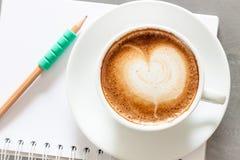 Copo de café com o bloco de notas no fundo cinzento Foto de Stock