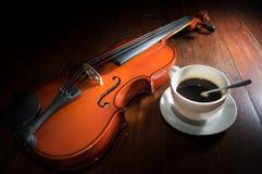 Copo de café com o violino na superfície da madeira Fotografia de Stock