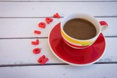 Copo de café com texto da argila vermelha na tabela de madeira fotografia de stock