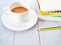 Copo de café com um livro e um lápis imagem de stock