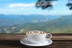 Copo de café com vapor em uma tabela de madeira foto de stock