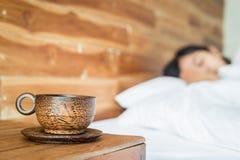Copo de café de madeira na tabela e nas mulheres na cama foto de stock royalty free