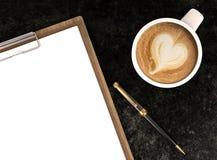 Copo de café do cappuccino com papéis vazios na pena da prancheta e de esferográfica, no café e no fundo do negócio Foto de Stock Royalty Free