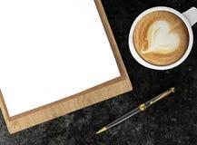 Copo de café do cappuccino com papéis vazios na pena da prancheta e de esferográfica, no café e no fundo do negócio Fotografia de Stock