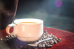 copo de café e backgrouds do bokeh dos feijões Foto de Stock Royalty Free