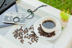 Copo de café e feijão de café na mesa com gadge fotos de stock royalty free