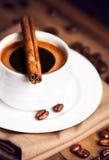Copo de café e feijões de café com as varas de canela na testa de madeira Imagem de Stock