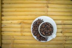 Copo de café e feijões de café no fundo de bambu Imagens de Stock Royalty Free