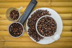 Copo de café e feijões de café no fundo de bambu Foto de Stock
