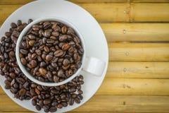 Copo de café e feijões de café no fundo de bambu Fotografia de Stock