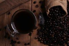 Copo de café e feijões de café no fundo de madeira Fotografia de Stock Royalty Free