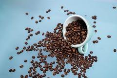 Copo de caf? e feij?es de caf? no fundo da cor imagens de stock royalty free