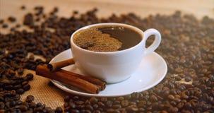 Copo de café e feijões de café Um copo branco do café de evaporação na tabela com feijão roasted Metragem conservada em estoque 4 video estoque
