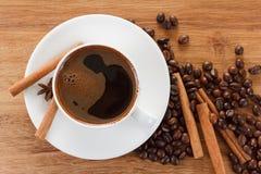 Copo de café e feijões, varas de canela, anis na tabela de madeira imagem de stock