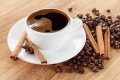 Copo de café e feijões, varas de canela, anis na tabela de madeira fotos de stock