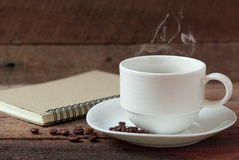Copo de café e livro de nota Fotografia de Stock Royalty Free