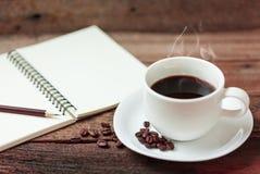 Copo de café e livro de nota Imagem de Stock Royalty Free