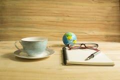 copo de café e livro de nota na tabela de madeira Fotos de Stock