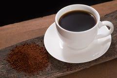 Copo de café e pó do café na madeira imagem de stock