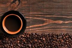 Copo de café e quadro dos feijões na tabela de madeira Fotos de Stock Royalty Free