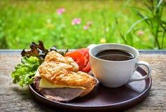 Copo de café e sanduíche do queijo do presunto Fotografia de Stock