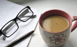 Copo de café e um pedaço de papel com uma pena de escrita e vidros em uma superfície clara trabalho Leia e edite o documento fotos de stock royalty free