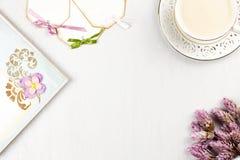 Copo de café elegante, livro de nota, etiquetas de papel e configuração do plano das flores Fundo feminino nas cores pastel Vista Fotos de Stock