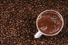 Copo de café em feijões de café no fim acima da foto imagem de stock royalty free