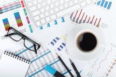 Copo de café em papéis financeiros fotografia de stock royalty free