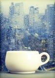 Copo de café em um dia chuvoso na frente da janela fotos de stock royalty free