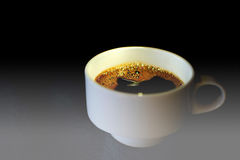 Copo de café em uma tabela de vidro Fim do copo de café branco acima com fundo escuro e luz dramática Fotografia de Stock Royalty Free