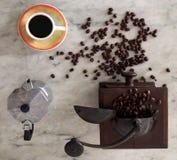 Copo de café, fabricante de café e moedor na tabela de mármore Fotos de Stock