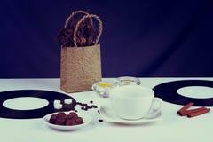 Copo de café, feijões de café e cubos vazios do açúcar em uma tabela Foto de Stock