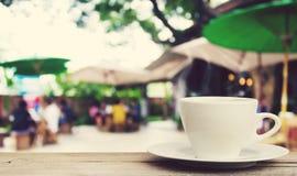 Copo de café na tabela de madeira com fundo da cafetaria do borrão Foto de Stock Royalty Free