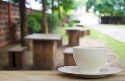 Copo de café na tabela de madeira com fundo da cafetaria do borrão imagens de stock