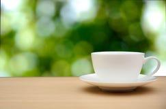 Copo de café na tabela de madeira fundo verde da natureza do bokeh imagem de stock