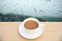Copo de café na tabela de madeira Fundos da gota da chuva da vista superior imagem de stock royalty free
